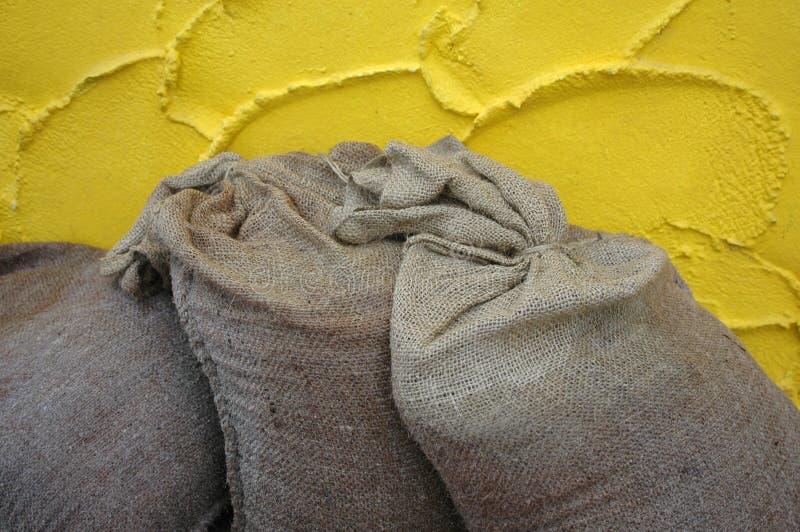 De zakken van het zand tegen de gele muur royalty-vrije stock afbeelding