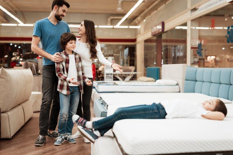De zalige familie koopt nieuwe orthopedische matras in meubilairopslag Gelukkige familie die matrassen in opslag kiezen royalty-vrije stock foto's