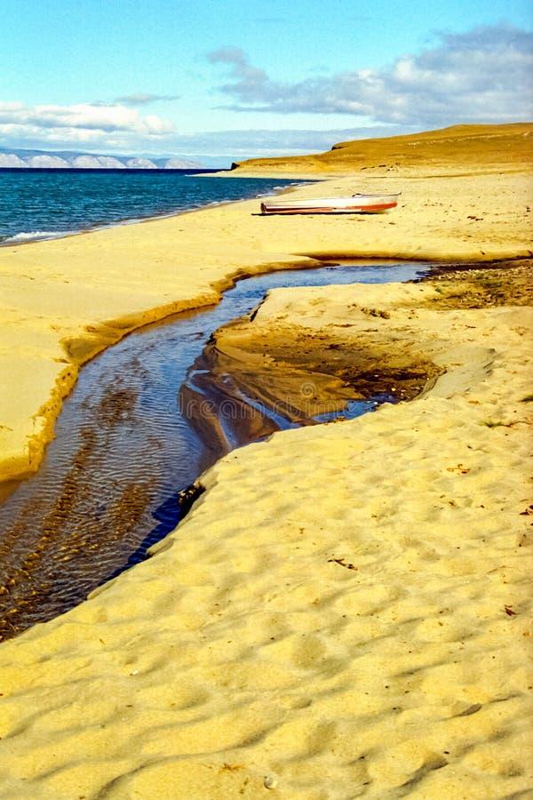De zandige kust van Baikal, een boot op de kust en een streamlet royalty-vrije stock foto