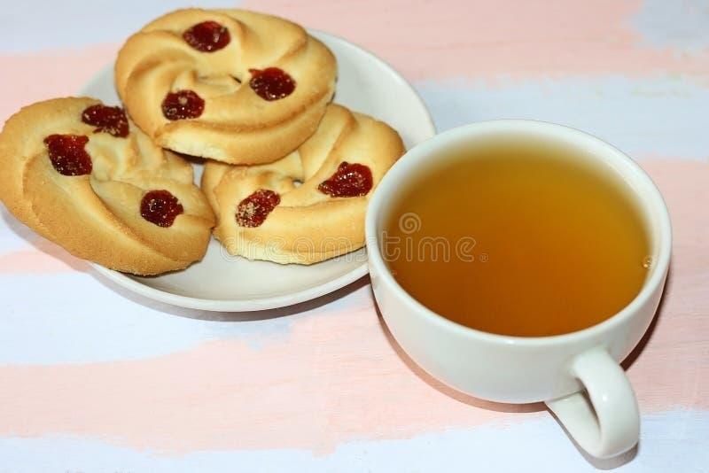 De zandkoekkoekjes met kers blokkeren en een mok groene thee op een roze-lichte blauwe houten lijst stock foto