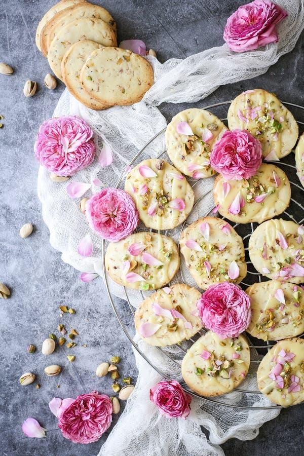 De zandkoekkoekjes met pistaches en namen bloemblaadjes toe stock fotografie