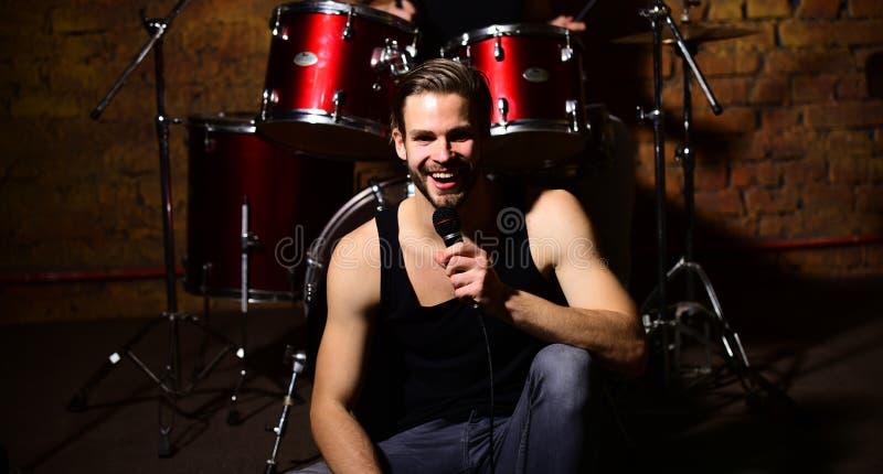 De zanger met vrolijk gezicht zingt zitting op scène vurige gitaar tegen zwarte achtergrond royalty-vrije stock foto's
