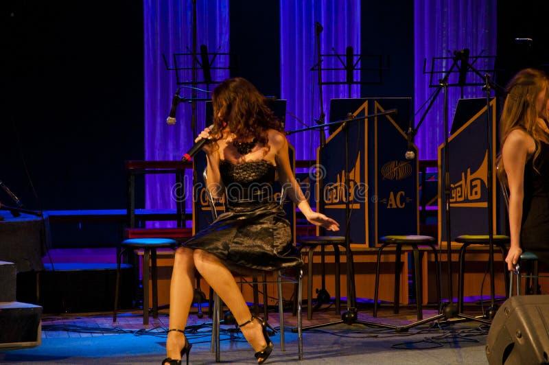 Jazz singer sexy vrouw in een zwarte cocktailjurk die zingt terwijl ze op stoel zit met microfoon elegantie en uiterlijk mode en  stock afbeeldingen