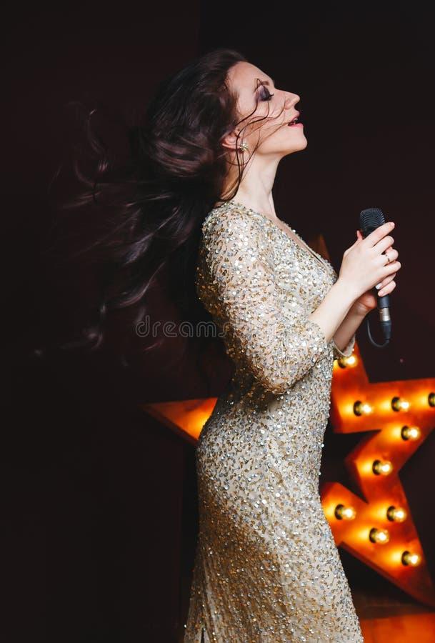 De zangervrouw in sexy schittert lange kleding op stadium met broadway ster op achtergrond Krullend kapsel, perfecte samenstellin stock afbeelding