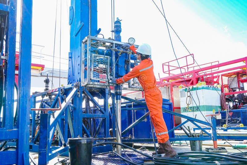 De zeebooreilandarbeider inspecteren en de vestigings hoogste zijhulpmiddelen eerst voor veiligheid op gevaarlijk gebied aan perf stock afbeeldingen