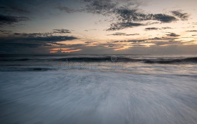 De zeegolven stroomden tijdens een dramatische zonsondergang op de kust royalty-vrije stock afbeelding