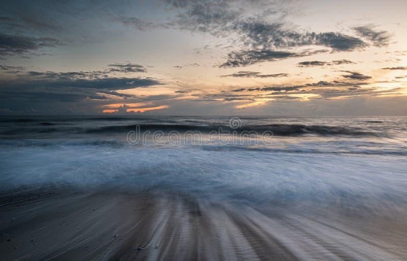 De zeegolven stroomden tijdens een dramatische zonsondergang op de kust stock foto's