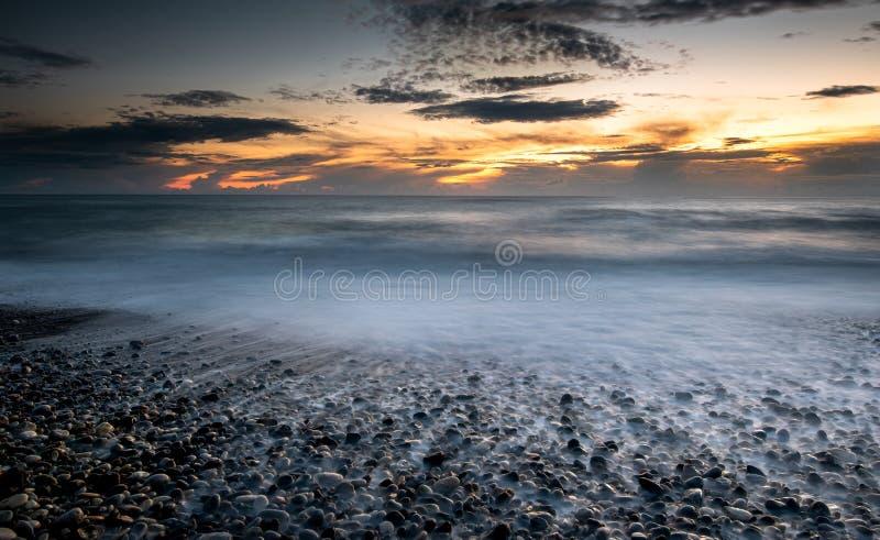 De zeegolven stroomden tijdens een dramatische zonsondergang op de kust royalty-vrije stock fotografie