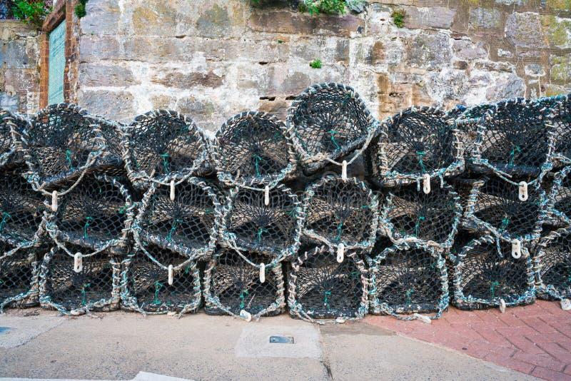 De zeekreeftpotten stapelden zich omhoog in de haven op stock foto