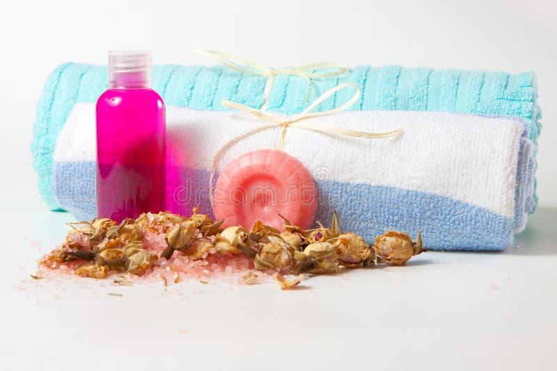 De zeep, de shampoo en de douche gelatineren met een handdoek, een overzees zout en rosebuds stock foto's