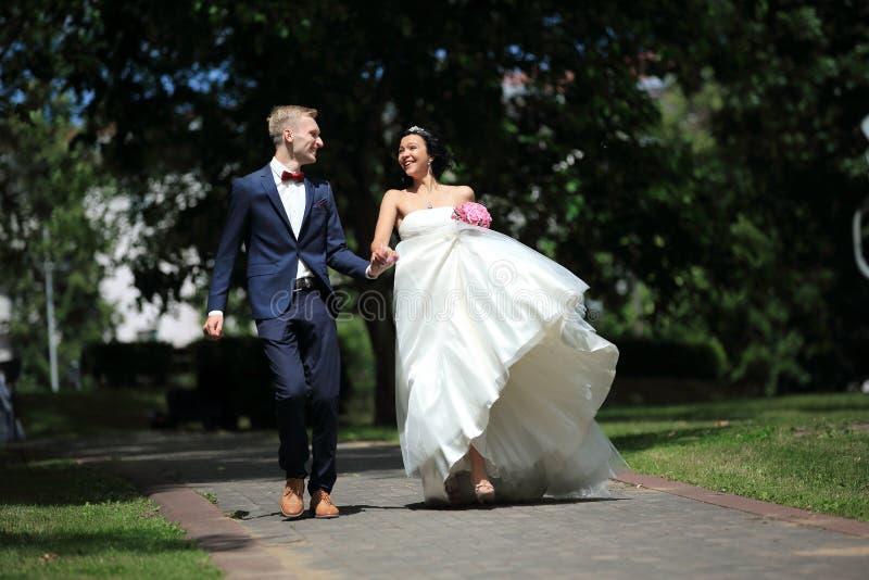 De zeer gelukkige gang van het jonggehuwdepaar in het Park royalty-vrije stock afbeeldingen