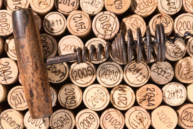 De zeer oude kurketrekker ligt op een achtergrond van vele verschillende uitstekend kurkt royalty-vrije stock afbeelding