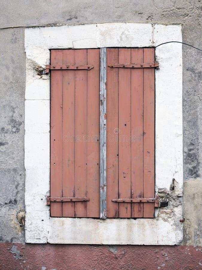 De zeer oude roodachtige bruine geschilderde blinden op venster in de middeleeuwse Provence huisvesten op luberongebied stock foto