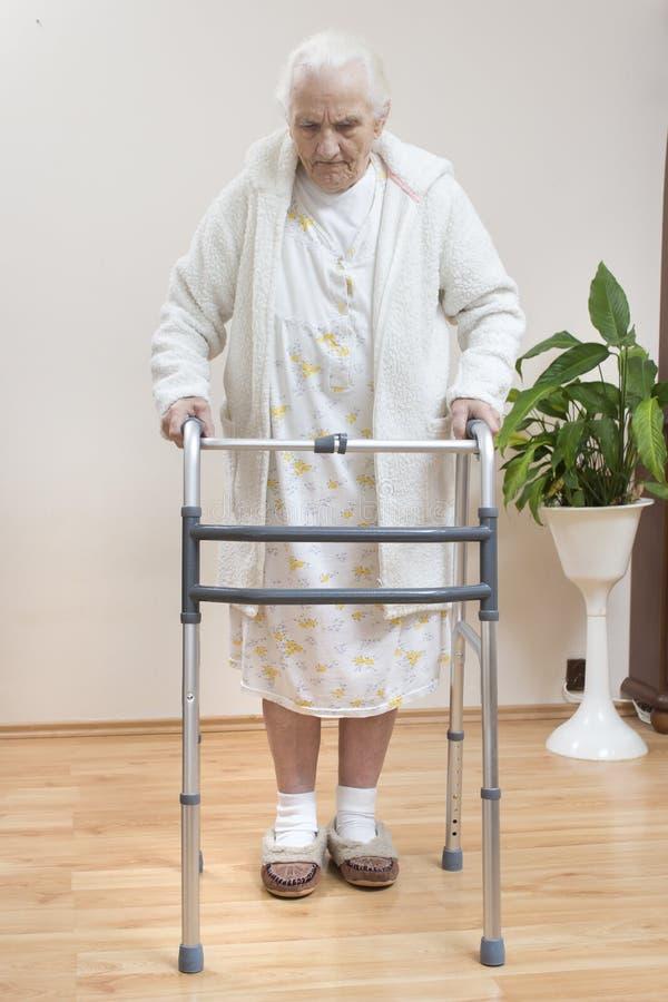 De zeer oude vrouw in een witte badjas en een nachtjapon gaat met behulp van een rehabilitatiebalkon stock fotografie