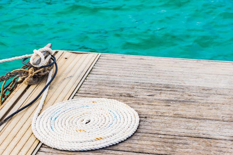 De zeevaartdiekabel van de meertroslijn op houten pier wordt gekruld stock foto