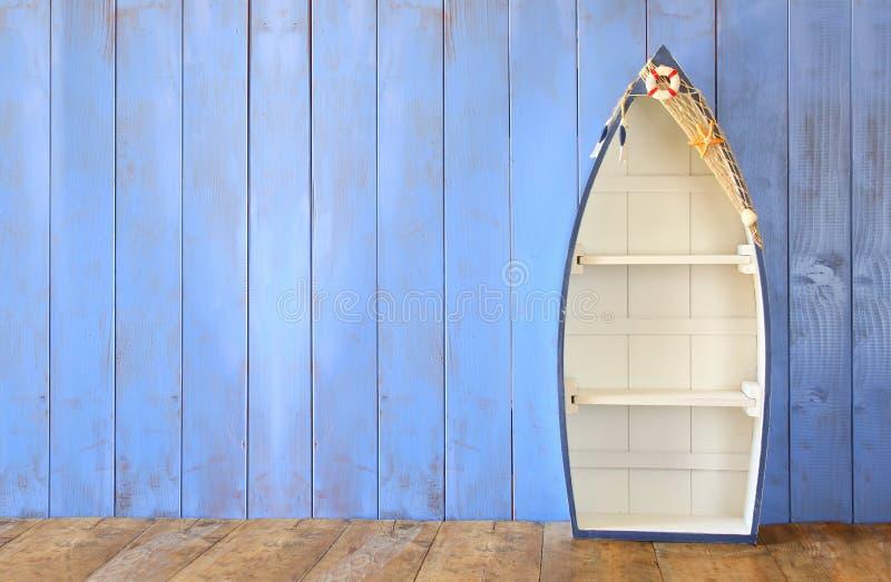 De zeevaartplanken van de bootvorm op houten lijst de achtergrond van de productvertoning, gefiltreerde wijnoogst stock foto