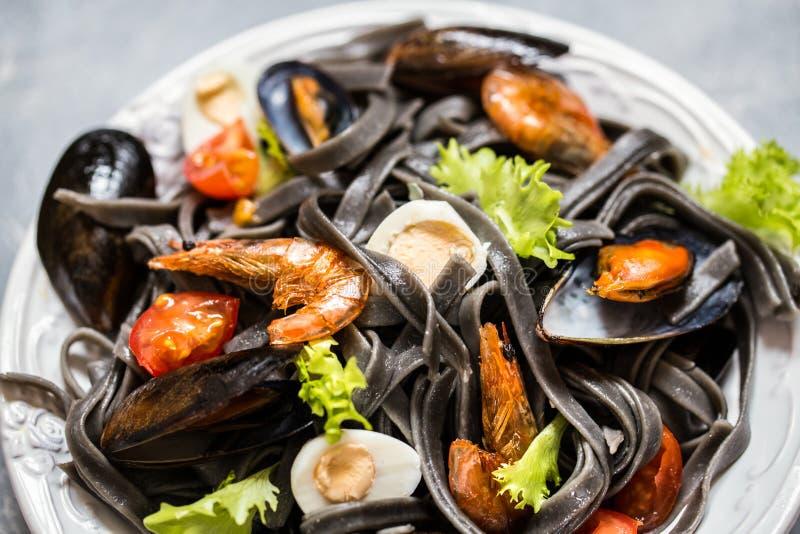 De zeevruchten met zwarte deegwaren, mosselen, garnalen en groenten royalty-vrije stock foto's