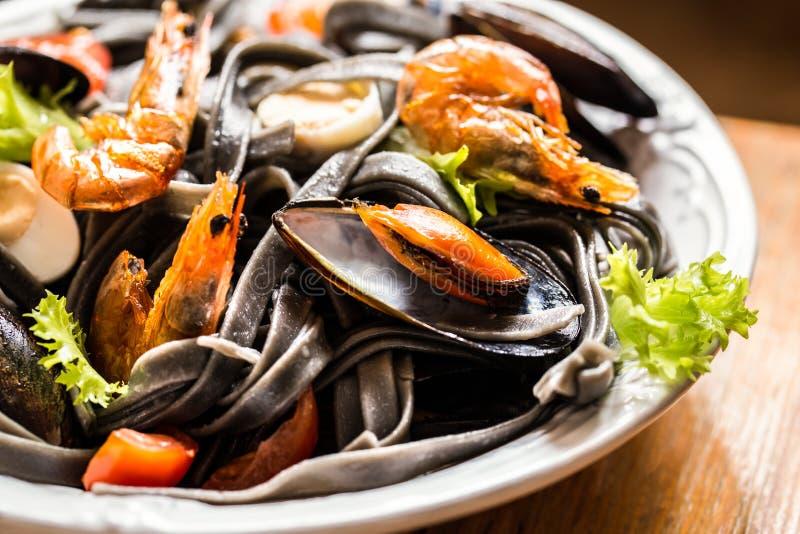 De zeevruchten met zwarte deegwaren, mosselen, garnalen en groenten stock afbeeldingen