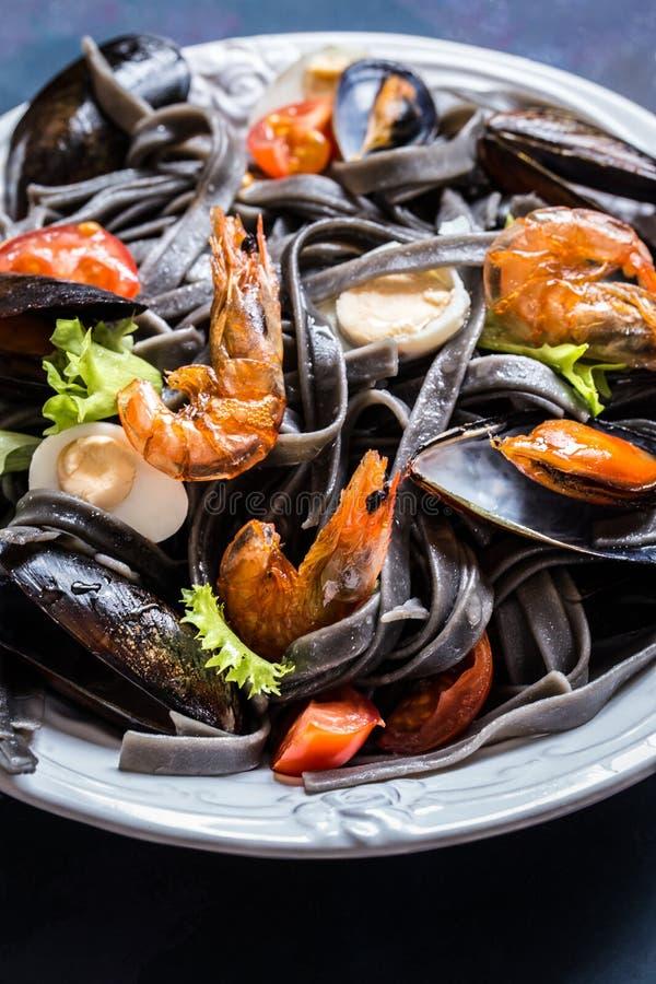 De zeevruchten met zwarte deegwaren, mosselen, garnalen en groenten stock fotografie