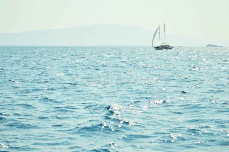 De de zeewateroppervlakte en golven rekken zich uit aan de horizon uit waar de eilanden ver weg zichtbaar zijn royalty-vrije stock afbeeldingen