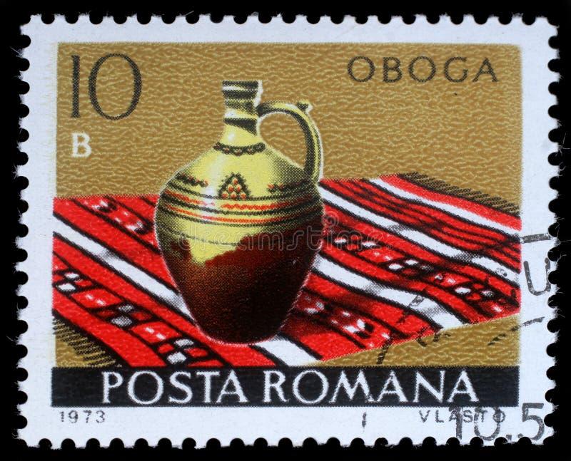 De zegel in Roemenië wordt gedrukt toont Oboga van het reeks Roemeense aardewerk dat stock foto's