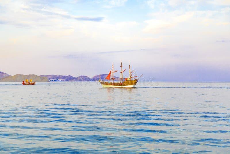 De zeilboot met scharlaken zeilen op het overzees gaat naar de kust stock foto