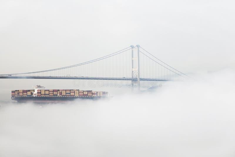 De zeilen van het containerschip in de mist royalty-vrije stock foto