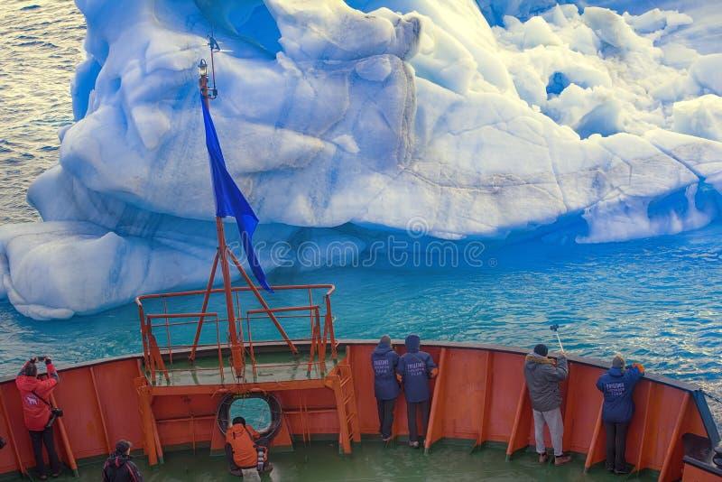 De zeilen van het toeristenschip dicht bij kleine ijsberg stock afbeeldingen