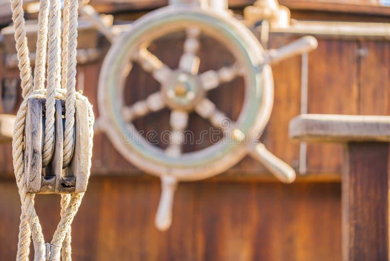 De zeilen, de zeevaartkatrol en het houten roer rijden op oud varend sloependek royalty-vrije stock fotografie
