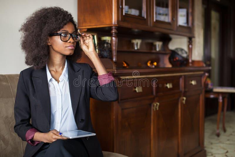 De zekere Afrikaanse onderneemster in oogglazen werkt aan de tablet terwijl het zitten op de bank royalty-vrije stock afbeeldingen