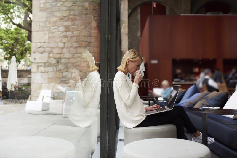 De zekere bedrijfsvrouw die nand laptop computerpuinkegel bekijken drinkt koffie royalty-vrije stock afbeeldingen