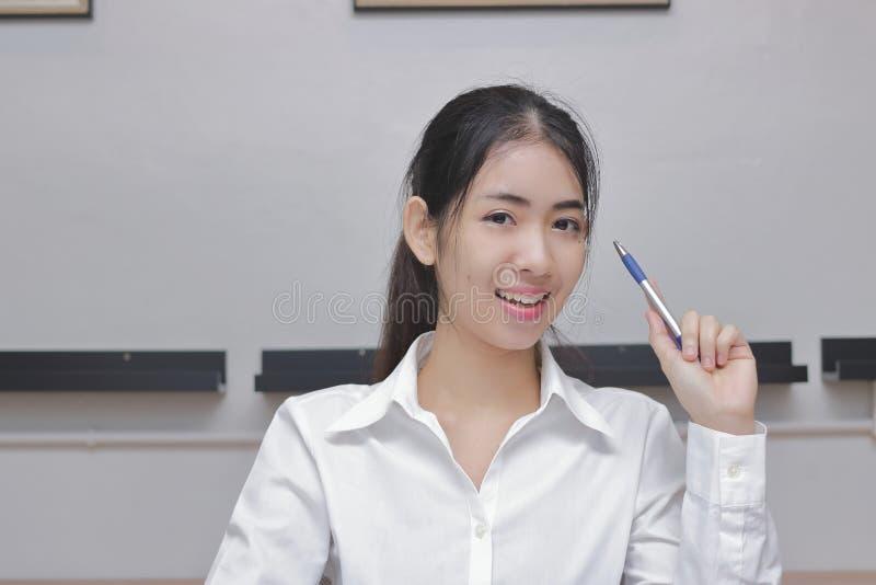 De zekere jonge Aziatische bedrijfsvrouw die een pen houden en heeft een idee bij woonkamer met exemplaar ruimteachtergrond stock foto's