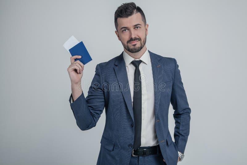 De zekere jonge bedrijfsmens in klassiek zwart kostuum, het paspoort van de overhemdsgreep, instapkaartkaartje isoleerde op grijz stock fotografie