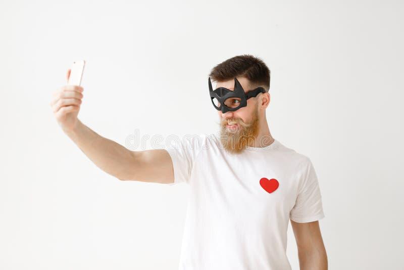 De zekere jonge mens met dik lange baard stelt bij camera van zijn moderne slimme telefoon zoals maakt selfie tegen witte studio stock afbeeldingen