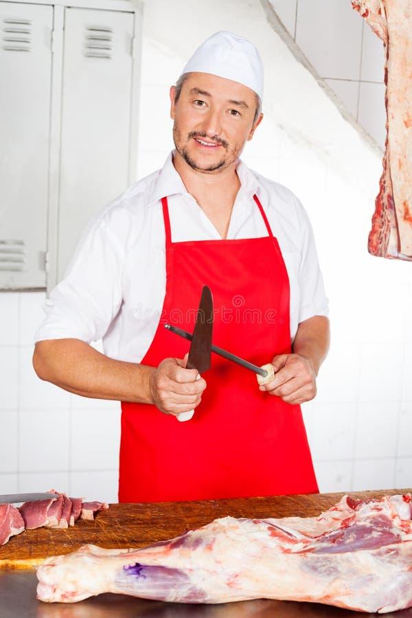 De zekere Slachterij van Slagerssharpening knife in stock foto's