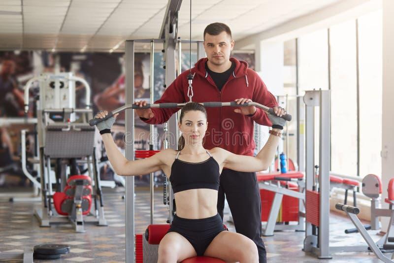 De zekere slanke mooie jonge dame zit op geschiktheidspost, doet lichaamsbewegingen, direct bekijkend camera Atletische lang royalty-vrije stock foto