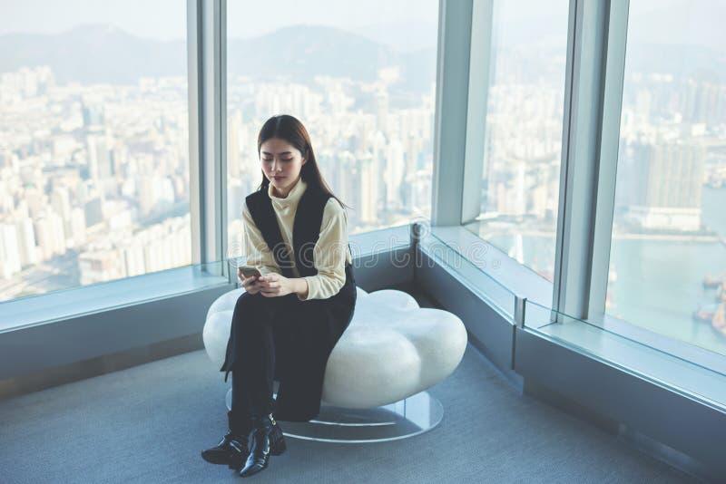 De zekere vrouwelijke secretaresse zoekt informatie over Web-pagina via celtelefoon tijdens het werkonderbreking stock foto