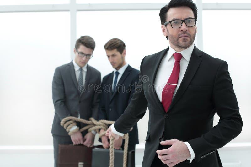 De zekere zakenman trekt de kabel gebonden werknemers stock foto