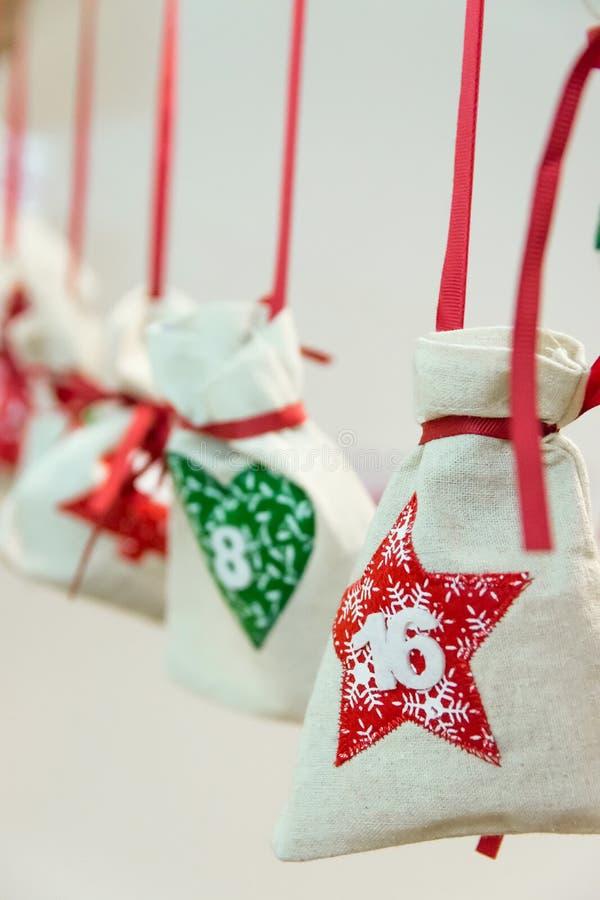 De zelf gemaakte het linnenzak van de Komstkalender met rood Kerstboomornament met 16 december-datum bond met zijdelint het hange stock afbeelding