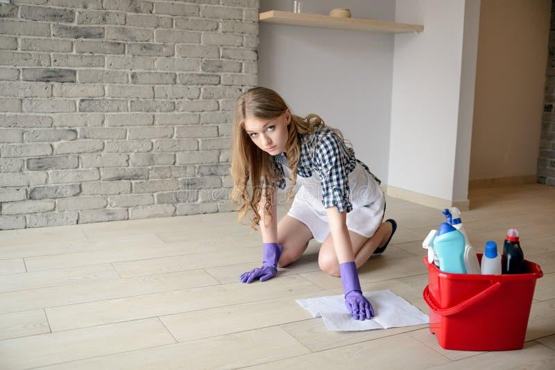 De zenuwachtige en vermoeide mooie jonge vrouw wast de vloer op haar knieën stock foto