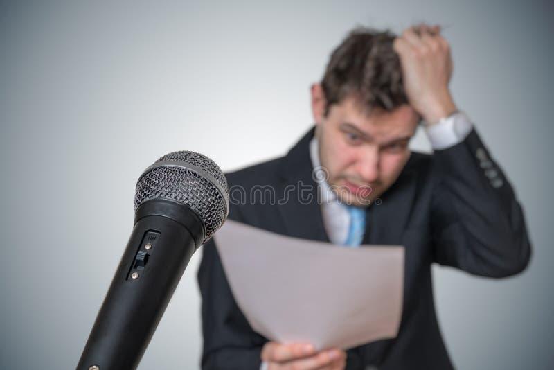 De zenuwachtige mens is bang van het openbare toespraak en zweten Microfoon vooraan royalty-vrije stock foto's