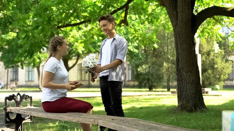 De zenuwachtige tiener die bloemen voorstellen aan mooi meisje in park, neemt meester op royalty-vrije stock fotografie