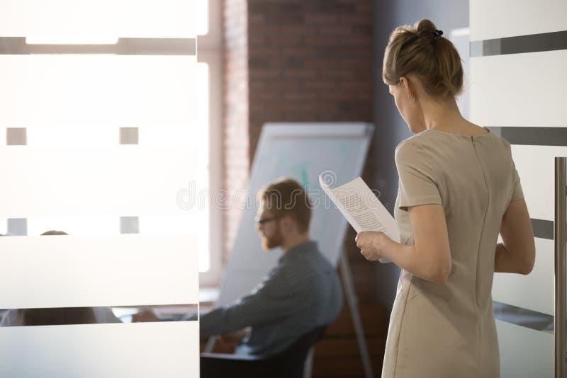 De zenuwachtige vrouwelijke doen schrikken werknemer sluit zich aan team bij vergadering in bureau royalty-vrije stock afbeelding