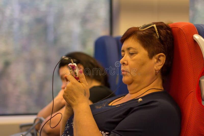 De zestig éénjarigenvrouw met mobiele telefoonritten in hogesnelheidstrein slikt in de zomer royalty-vrije stock afbeeldingen
