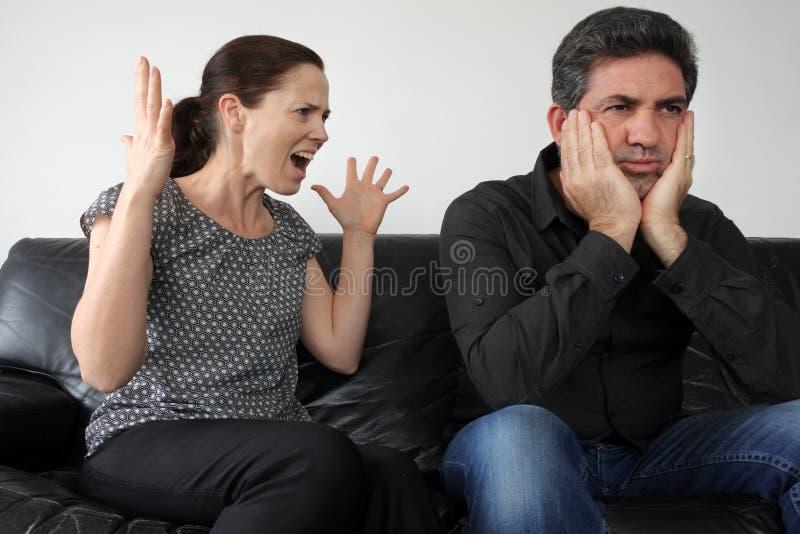 De zeurderige vrouw klaagt aan haar echtgenoot stock afbeeldingen