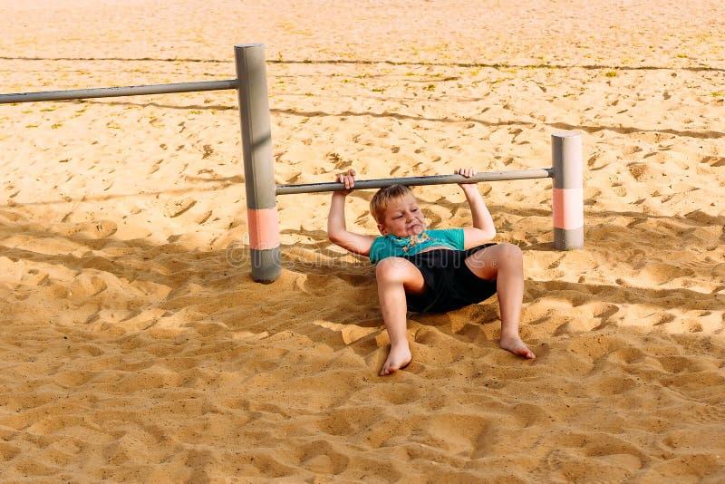 De zeven-jaar-oude jongen is bezet op straatrekstokken op het strand stock afbeeldingen