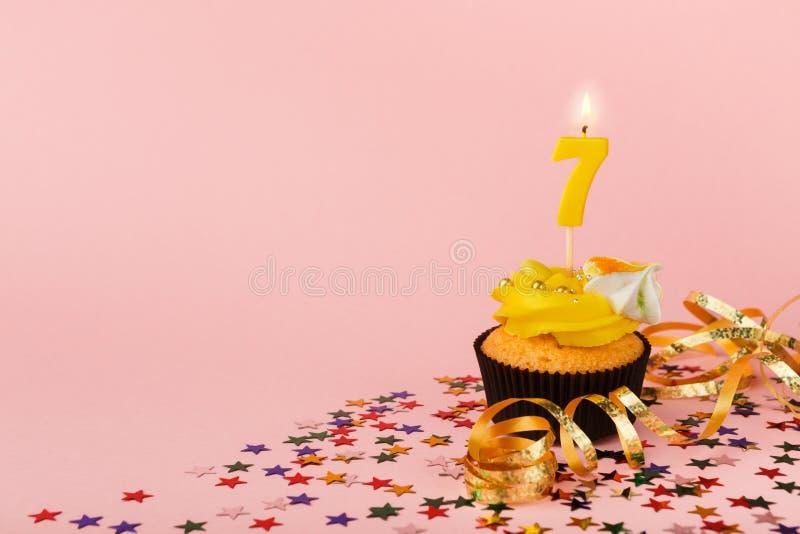 De zevende verjaardag cupcake met kaars en bestrooit stock foto's