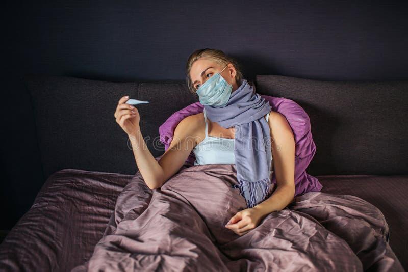 De zieke jonge vrouw in masker ligt op bed en bekijkt thermometer Zij houdt het in één hand Droevig en verstoorde vrouw Zij is royalty-vrije stock afbeelding
