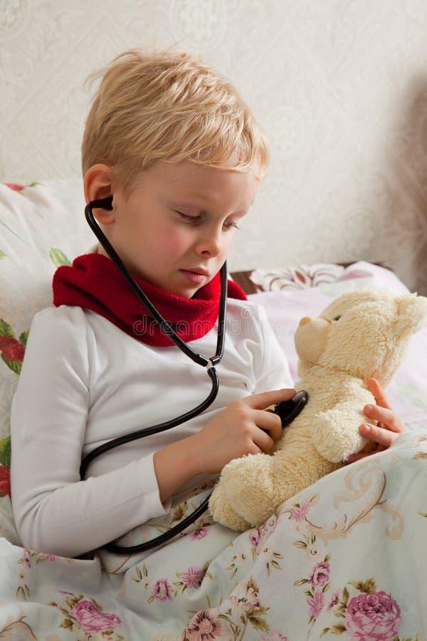 De zieke jongen speelt met een stethoscoop stock afbeelding