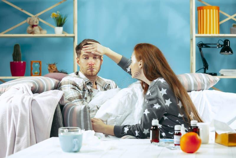 De zieke mens met koorts die in bed ligt dat temperatuurmeisje heeft neemt zorg voor hem royalty-vrije stock foto's
